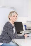 Привлекательный женский менеджер в портрете усмехаясь на камере стоковая фотография