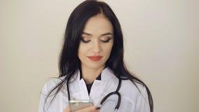 Привлекательный женский доктор используя мобильный телефон на предпосылке 4K сток-видео