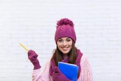 Привлекательный жест рукой девушки студента для того чтобы скопировать улыбку космоса в розовой шляпе держа карандаш папки Стоковые Фото