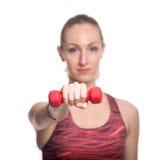 Привлекательный жизнерадостный молодой фитнес делая разминку с красными гантелями Изолировано над белой предпосылкой Стоковые Изображения
