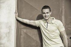 Привлекательный зеленый цвет наблюдал склонность молодого человека против стены снаружи Стоковые Фотографии RF