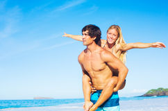 привлекательный играть piggyback пар пляжа стоковое изображение rf