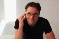 Привлекательный и расслабленный человек усмехаясь пока телефонный звонок Стоковые Изображения RF