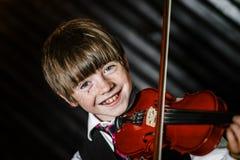 Привлекательный мальчик играя скрипку, стрельбу студии стоковые фотографии rf
