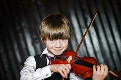 Привлекательный мальчик играя скрипку, стрельбу студии стоковое фото