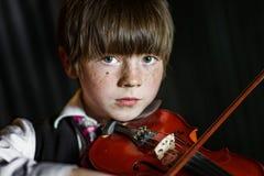 Привлекательный мальчик играя скрипку, стрельбу студии стоковые изображения
