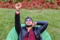 Привлекательный молодой арабский мусульманский человек лежит на стуле и мечтать, глоточек стоковые изображения rf
