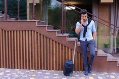 Привлекательный молодой арабский человек стоя с чемоданом в руке и p Стоковые Фотографии RF