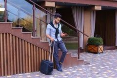 Привлекательный молодой арабский человек стоя с чемоданом в руке и p Стоковые Фото