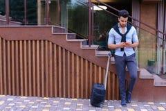 Привлекательный молодой арабский человек стоя с чемоданом в руке и p Стоковое Изображение RF