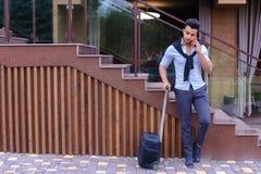 Привлекательный молодой арабский человек стоя с чемоданом в руке и p Стоковое фото RF