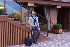 Привлекательный молодой арабский человек стоя с чемоданом в руке и p Стоковые Изображения RF
