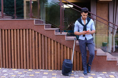 Привлекательный молодой арабский человек стоя с чемоданом в руке и p Стоковое Изображение