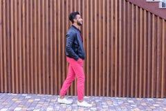 Привлекательный молодой аравийский человек смотрит вокруг и прогулки, усмехаются стоковое фото