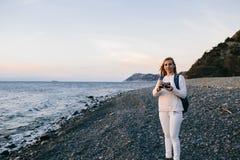 привлекательный молодой белокурый путешественник женщины стоя с ретро камерой на пляже Стоковые Изображения RF