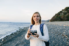 привлекательный молодой белокурый путешественник женщины стоя с ретро камерой на пляже Стоковые Изображения