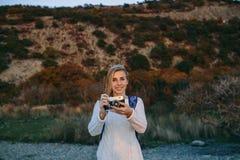 Привлекательный молодой белокурый турист женщины стоя с ретро камерой в руках внешних Стоковое Изображение RF