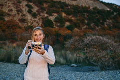 Привлекательный молодой белокурый турист женщины стоя с ретро камерой в руках внешних Стоковое Изображение