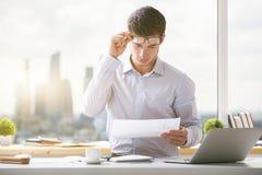 Привлекательный молодой бизнесмен делая обработку документов Стоковые Изображения