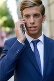 Привлекательный молодой бизнесмен на телефоне в городской предпосылке Стоковые Изображения