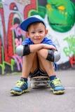 Привлекательный молодой мальчик сидя на его скейтборде Стоковые Изображения