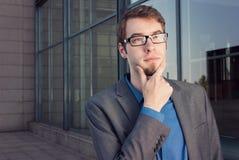 Привлекательный молодой думать бизнесмена стоковое изображение