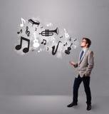 Привлекательный молодой человек пея и слушая к нот с мюзикл Стоковая Фотография