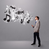Привлекательный молодой человек пея и слушая к нот с мюзикл Стоковые Фото