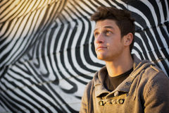 Привлекательный молодой человек стоя против зебры Стоковые Изображения