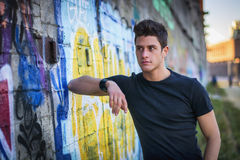 Привлекательный молодой человек стоя против красочного стоковые фото