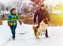 Привлекательный молодые мальчик и девушка играя с собакой Стоковые Фотографии RF
