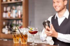 Привлекательный мужской бармен трясет питье в пабе стоковое фото