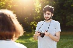 Привлекательный мужчина при борода и стильный hairdo делая фото его подруги которая представляет на природе смотря изображения ко Стоковое фото RF