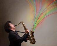 Привлекательный музыкант играя на саксофоне пока красочный конспект Стоковая Фотография