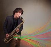Привлекательный музыкант играя на саксофоне пока красочный конспект Стоковое Изображение RF