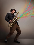 Привлекательный музыкант играя на саксофоне пока цветастый конспект Стоковая Фотография