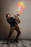Привлекательный музыкант играя на саксофоне с красочным конспектом стоковые фото