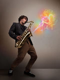 Привлекательный музыкант играя на саксофоне с цветастым конспектом стоковое изображение