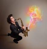 Привлекательный музыкант играя на саксофоне с цветастым конспектом стоковые изображения rf