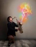 Привлекательный музыкант играя на саксофоне с цветастым конспектом стоковое фото rf