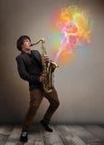 Привлекательный музыкант играя на саксофоне с цветастым конспектом стоковое фото