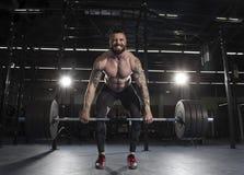 Привлекательный мышечный культурист делая тяжелую тренировку deadlift внутри стоковая фотография rf