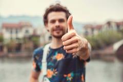 Привлекательный отдыхая человек с большим пальцем руки вверх Уверенное озеро стороны и красивые коттеджи на предпосылке Стоковое Изображение RF