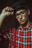 Привлекательный парень в стеклах исправляет его крышку Стоковая Фотография RF