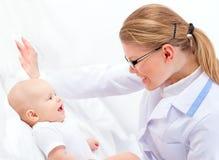 Привлекательный содружественный доктор Терапевт Рассматривать Младенец Tummy женщины Стоковое Изображение