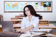 Привлекательный студент печатая на компьтер-книжке в классе Стоковое Изображение RF