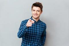 Привлекательный счастливый молодой человек стоя над серой стеной и указывать стоковое фото