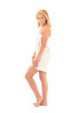 Привлекательный усмехаться белокурый в полотенце представляя над белизной Стоковая Фотография