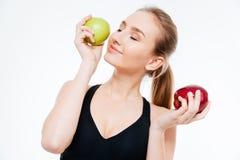 Привлекательный усмехаясь спортсмен женщины представляя с красными и зелеными яблоками Стоковые Изображения