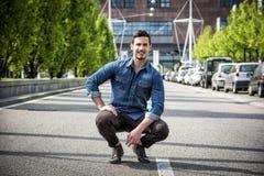 Привлекательный усмехаясь человек сидя в середине дороги города стоковые фотографии rf